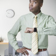 Photo: African businessman holding up watch and frowning