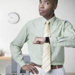 Africký podnikatel, mračil se a zvedl hodinky — Stock fotografie