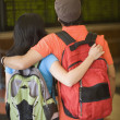 Photo: Young couple wearing backpacks
