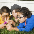 Mixed Race children playing with magnifying glass — Stock Photo