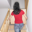 Woman carrying box up stairs in new house — Stock Photo
