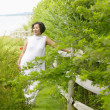 Pregnant woman standing by fence — Stock Photo