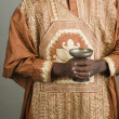 African man wearing traditional dress and holding chalice - Stock Photo