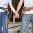 Couple holding hands and wearing tool belts — Stock Photo #13224956