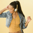 Studio shot of a Dominican woman dancing and wearing headphones — Stock Photo