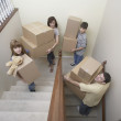Family carrying moving boxes up stairs — Stock Photo
