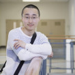 Male Asian student leaning on railing — Stockfoto