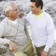 Hispanic father and adult son smiling at each other - Stock Photo
