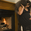 Pregnant couple in fancy clothing hugging next to fireplace - Stock Photo