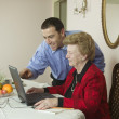 Son helping mom with laptop — Stockfoto