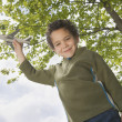 Boy standing outside with toy plane - Stock Photo