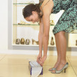 Stock Photo: Young woman trying on shoes