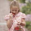 Royalty-Free Stock Photo: Young girl eating strawberry from pail outdoors