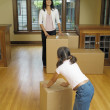 Young girl pushing a box on a hardwood floor — Stock Photo