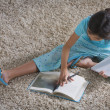Young Hispanic girl doing homework on the floor — Stock Photo