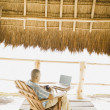 Foto Stock: Young musing laptop underneath thatch roof on beach