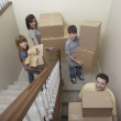Family carrying moving boxes down stairs — Stock Photo