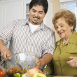 Stock Photo: Hispanic mother and adult son preparing food in kitchen
