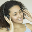 Close up of African woman listening to headphones — Stockfoto