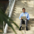 Businessman with laptop sitting on step — Stock Photo