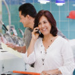 Hispanic woman on cell phone in grocery store - Stock Photo