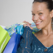 Portrait of woman smiling with gift bags over shoulder — Stock Photo