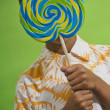 African boy holding big lollipop over face - Stockfoto
