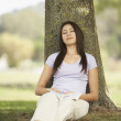 Hispanic woman resting against tree — Stock Photo