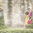 Three women next to ivy covered stone wall - Foto de Stock