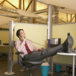 Businessman talking on phone with feet on desk — Stockfoto