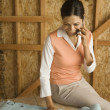 Hispanic woman talking on cell phone at construction site — Stock Photo