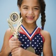Hispanic girl smiling with medal and trophy — Stock Photo