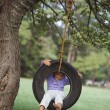 Young girl sitting in tire swing — Stock Photo #13225455