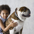Portrait of young girl hugging bulldog — Stock Photo
