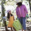 Mother and daughter carrying gardening supplies outdoors — Stock Photo
