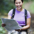 Woman wearing backpack reading map — Stock Photo