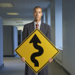 Businessman holding curves ahead sign — Stock Photo
