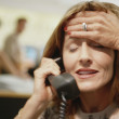 Businesswoman on telephone with her hand on her head - Stock Photo