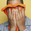 Stock Photo: Africmin pajamas holding washcloth to face