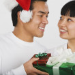 Asian couple exchanging Christmas gifts — Stock Photo