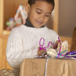 Stock Photo: Boy wrapping gift for mom