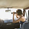 Hispanic womlooking through binoculars in car — Stock Photo #13225746