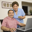 Senior Hispanic couple with credit card and laptop — Stock Photo
