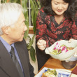 Asian woman serving her father at the dinner table - Stock Photo