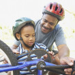 African American father helping son fix bicycle - Stock Photo