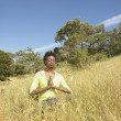 Woman meditating in field — Stock Photo #13225839
