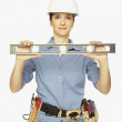 Hispanic female construction worker holding level — Stock Photo #13225841