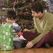 Stock Photo: Hispanic father watching son open Christmas gift