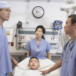 Asian boy in hospital bed with doctors talking - Stok fotoğraf