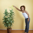 Portrait of woman watering plant — Stock Photo